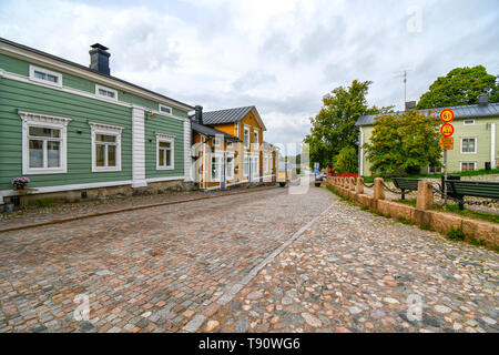 Colorful buildings line the cobblestone streets at the entrance to the medieval village of Porvoo, Finland. - Stock Image