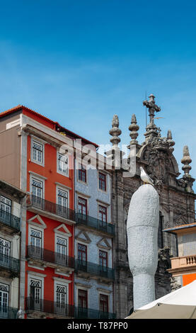Picturesque colorful houses covered in azulejo tiles in Porto with a baroque style church on far right - Stock Image