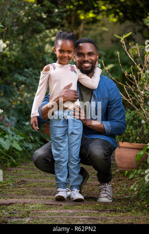 A man holding his daughter in a garden - Stock Image