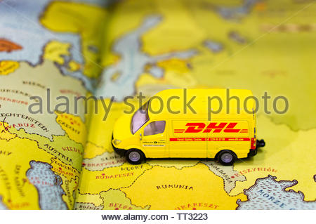 Siku toy model DHL transport van on a open book with maps on circa June 2019 in Poznan, Poland. - Stock Image