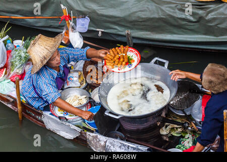Damnoen Saduak - 4th March 2014: Women vendors frying spring rolls. The town is famous for its floating market. - Stock Image