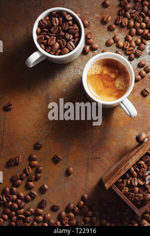 Cup of espresso with coffee beans scattered over a rustic surface. - Stock Image