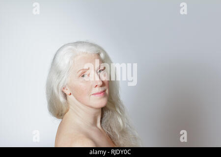 Headshot of an attractive mature woman with beautiful long gray hair in front of white background, copy space. - Stock Image