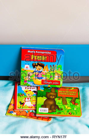 Poznan, Poland - November 18, 2018: Colorful child book about laundry on a blue bed. - Stock Image