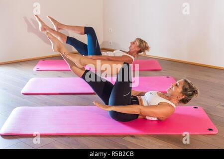 Women practicing pilates exercises. - Stock Image