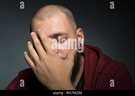 Man with eyes closed covering face with hands - Stock Image