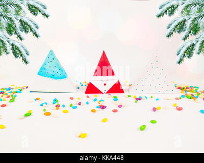 Christmas decoration triangle gift boxes with colorful candies from the box with christmas trees for celebrations - Stock Image