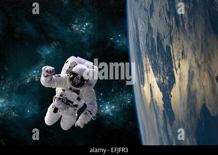An artist's depiction of an astronaut floating in space while orbiting a large, Earth-like planet. - Stock Image