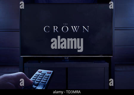A man points a TV remote at the television which displays the Crown main title screen (Editorial use only). - Stock Image