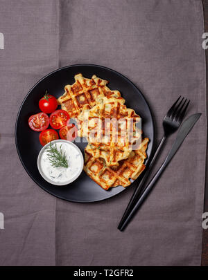 healthy breakfast. savory potato dill waffles with tomatoes, tzatziki on a black plate - Stock Image