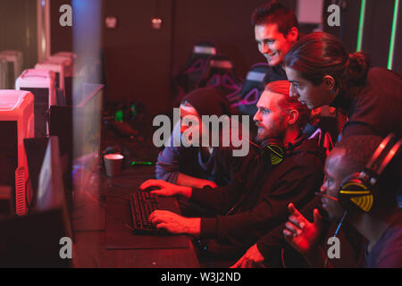 Group of focused young men standing together in front of computer monitor and playing video game, friends assisting guy to pass network game - Stock Image