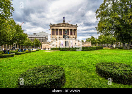 Tourists visit the National Gallery or Altes Nationalgalerie on an overcast day on Museum Island in Berlin Germany. - Stock Image