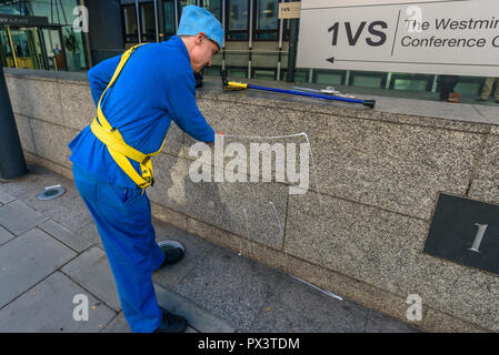 London, UK. October 19th, 2018. 'Commander Neil Godwin Tracy' of International Rescue squirts paste on the wall of  the Dept for Business, Energy and Industrial Strategy (BEIS) after he had been refused entry. He had come to offer his organisation's assistance, to produce policies which which recognise the desperate need to cut carbon emissions to avoid disastrous global warming and climate change by banning all fracking.  lock Credit: Peter Marshall/Alamy Live News - Stock Image