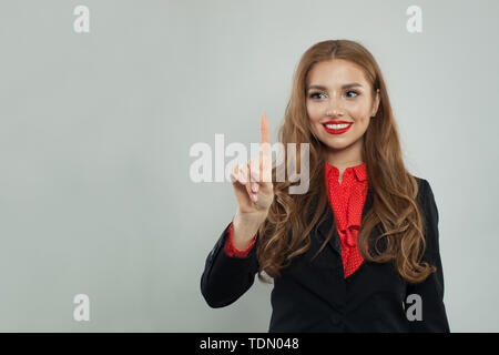 Happy businesswoman pointing her finger to empty copy space on gray banner background - Stock Image