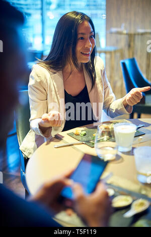 Smiling business woman sitting in bar - Stock Image
