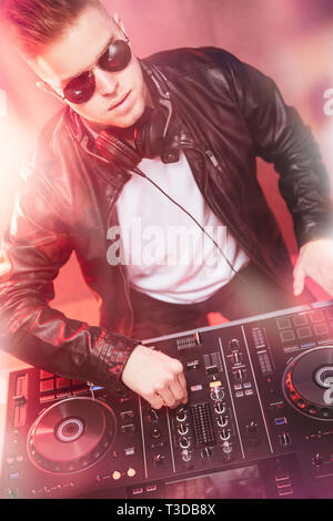 Dj mixing at party festival with red light and smoke in background - Summer nightlife view of disco club inside. Focus on face - Stock Image