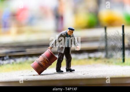 Miniature model of a man pulling an oil drum, at Kolejkowo, Wrocław, Wroclaw, Wroklaw, Poland - Stock Image