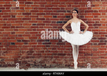 Young ballet dancer wearing pink standing with hands on the hip in dance studio, full length photo. copy space - Stock Image