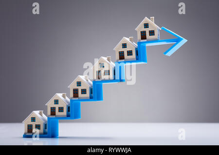 Small Model House On The Increasing Staircase Blue Arrow Over White Desk - Stock Image