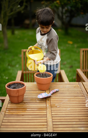 Boy plants seeds in flower pots and waters them - Stock Image