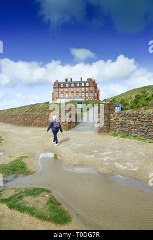 A female walker on the coastal path near the Headland Hotel in Newquay in Cornwall. - Stock Image