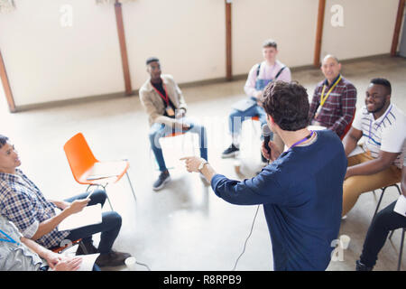 Man with microphone talking to men in group therapy - Stock Image