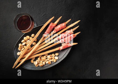Prosciutto-wrapped Italian grissini with wine and roasted almonds, shot from the top. Italian antipasti with parma ham, overhead photo on black - Stock Image
