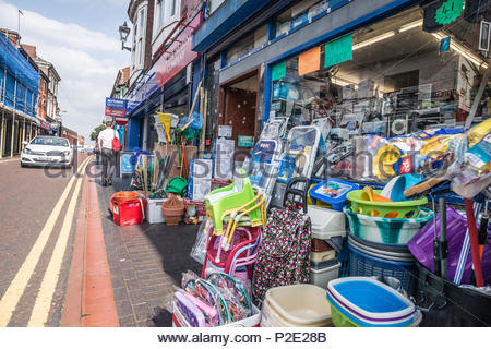 Shop front. A jumble of household retail products including plastic bowls and washing baskets, cleaning equipment, step ladders and plastic chairs, ou - Stock Image