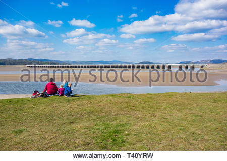 A family having a picnic overlooking the Kent Viaduct by the attractive seaside village of Arnside, Cumbria, England, UK on the Kent Estuary - Stock Image