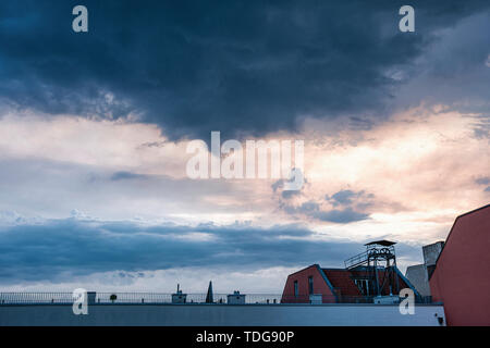 Stormy sky, clouds of approaching storm over Apartment building rooftop at sunset in Berlin - Stock Image