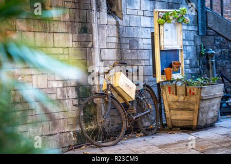 Vintage Bike Selective Focus around Flowers and Decorative Boxes - Stock Image