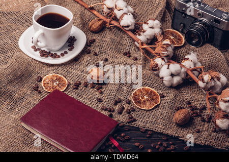 Coffee in a cup of notebook retro camera and cotton in a still-life in a rustic style - Stock Image