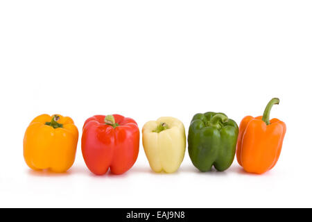 Five different coloured peppers in a row isolated on white - Stock Image