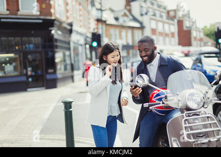 Young couple using cell phone at motor scooter on sunny urban street - Stock Image