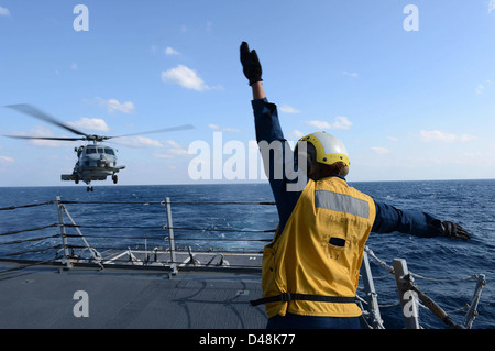 A Sailors signals to an SH-60B Sea Hawk helicopter. - Stock Image
