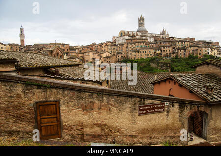 world heritage site Siena Italy skyline view with its magnificent medieval architecture and dome and ancient rooftops against a pale blue sky - Stock Image