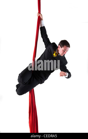 photograph of businessman checking his watch while hanging from red sash - Stock Image