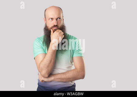 Portrait of confused middle aged bald man with long beard in light green t-shirt standing with hand on chin and looking away and thinking what to do. - Stock Image