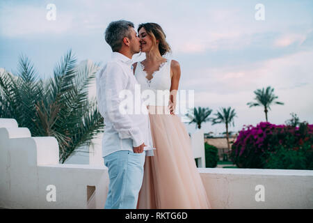Happy newlyweds kiss on terrace of white villa against background of palms branches and flowers during the honeymoon in Egypt. - Stock Image