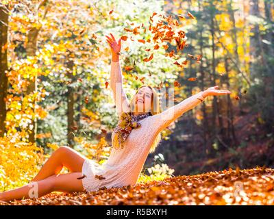 Adolescent teenager girl pretty natural in nature throwing upwards fallen leaves foliage - Stock Image