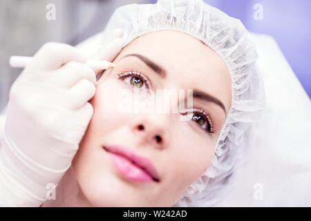 Beauty technician using pencil to mark woman's face for beauty treatment. - Stock Image