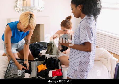 Young women friends packing for spring break in bedroom - Stock Image