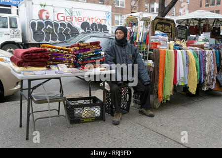 An Islamic vendor selling fabrics and religious articles at an outdoor stand on 37th Avenue in Jackson Heights, Queens, New York City. - Stock Image
