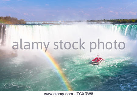 The Horseshoe Fall in the Niagara Falls. A beautiful rainbow appears in the foreground. The Hornblower cruise is approaching the falling water which r - Stock Image