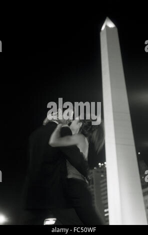 Couple romantically embracing near Obelisk on Avenida 9 de Julio in Buenos Aires at night - Stock Image