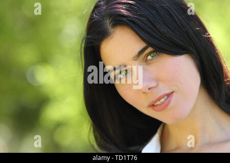 Portrait of a beauty woman with green eyes looking at you in a park with a unfocused background - Stock Image