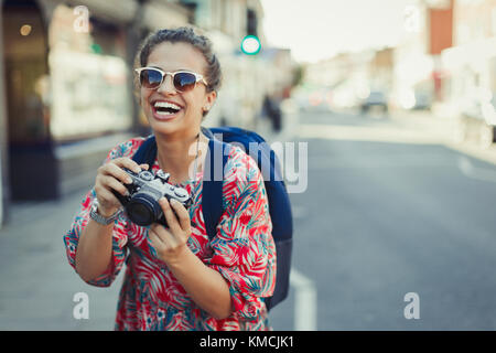 Portrait laughing, enthusiastic young female tourist in sunglasses photographing with camera on urban street - Stock Image