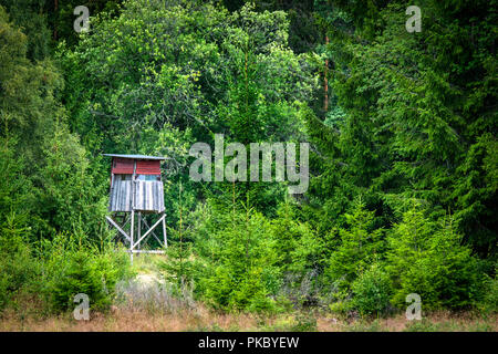 Wooden hunting tower in a green forest in the summer with red painted planks - Stock Image