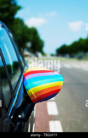 closeup of a rainbow flag in the wing mirror of a car on the street - Stock Image