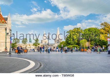 Matthias Square with the Matthias Church and the Fisherman's Bastion with tourists enjoying the sunny day in Budapest Hungary - Stock Image